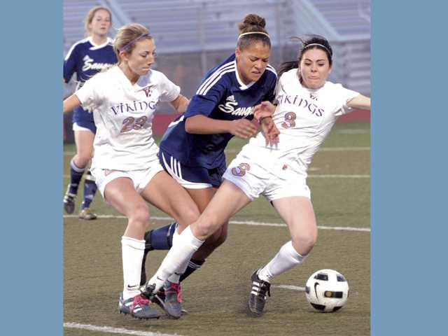 Saugus High's Angie Weiner, center, collides with Valencia High defenders Taylor Venegas, left, and Brooklyn Stevens at Valencia High on Friday.