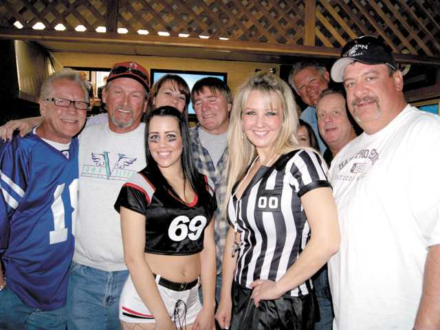 Schoonerville sports fans gather around Marcy Fischer, right, and her daughter Kristina on Sunday as the Super Bowl game is about to begin.