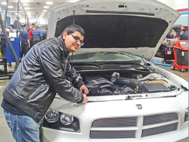 Bowman High School student Arjun Malhotra helps fix a car as part of a recent field trip to Universal Technical Institute in Rancho Cucamonga.