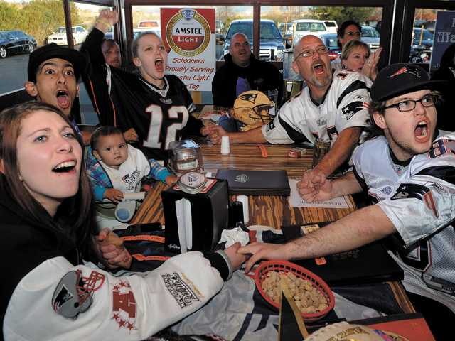 From left, Brittney Schmidt, Robert Garcia, 1-year-old Lilly Grace Garcia, Adrianna Pyles, Kevin Pyles and Christian Pyles celebrate at New England Patriots touchdown at the end of the first half during the Super Bowl at Schooners Patio Grille in Santa Clarita.