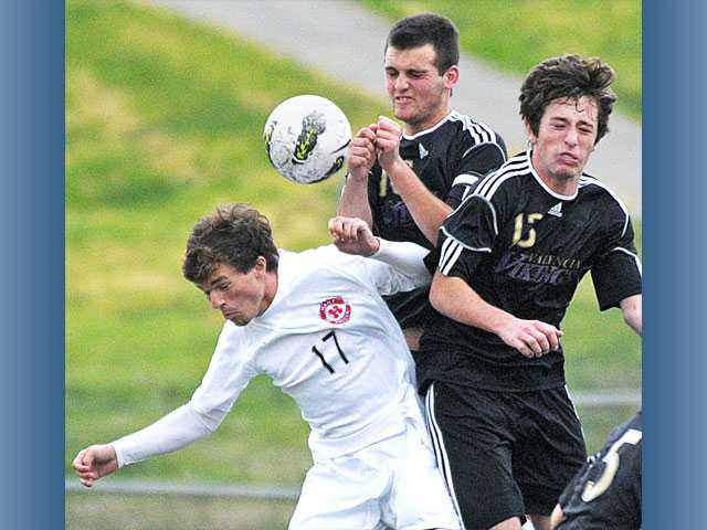 Hart's Jordan Karroll (17) collides with Valencia's Garrett McPheeters, center, and Jake Veiga on Tuesday at Hart High.