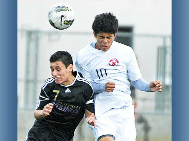Valencia's Jesus Fernandez (7) battles for a header with Hart's Eduardo Ojeda on Tuesday at Hart High.