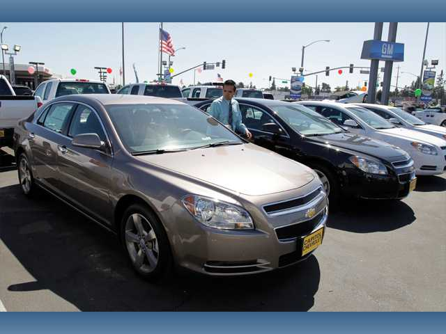 In this Aug. 30 photo, 2011 Chevrolet Malibus are lined up at a car dealership in San Jose.