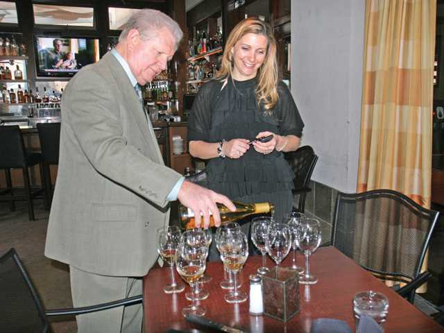 Carl Kanowsky, left, pours the 2010 Novy Willamette Valley Blanc de Pinot Noir for Jennifer Chadwick of Salt Creek Grille.