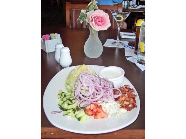 The Oaks Grille signature Iceberg Wedge salad. This Wedge is smothered in cucumbers, tomatoes, red onions, crumbled blue cheese and bacon. It is served with buttermilk ranch dressing.