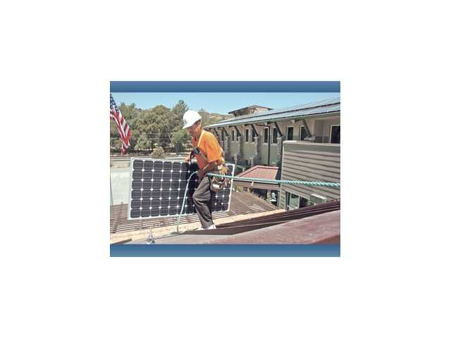 Installer Javier Alvarado carries one of 202 solar panels to be placed on the roof of the Newhall County Water District Administration building in Newhall in 2010.