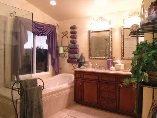 An elegant master bathroom can be as romantic as any room in the house with the addition of candles in holders on the walls, luxurious towels and soft lighting.