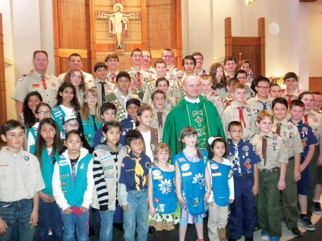 Local Boy Scouts and Girl Scouts surround Father Olin Mayfield at St. Clare Catholic Church in Canyon Country during the annual Scout Sunday Mass celebrated on Feb. 6.