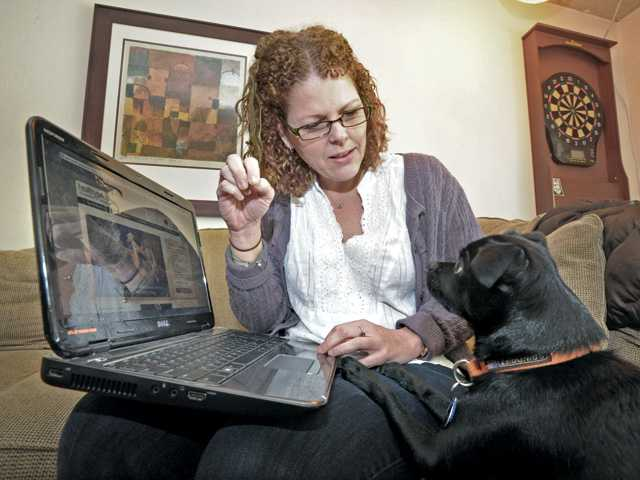 Leeanne Shinn holds a treat for 2-year old terrier-pug, Scout in their Valencia home.