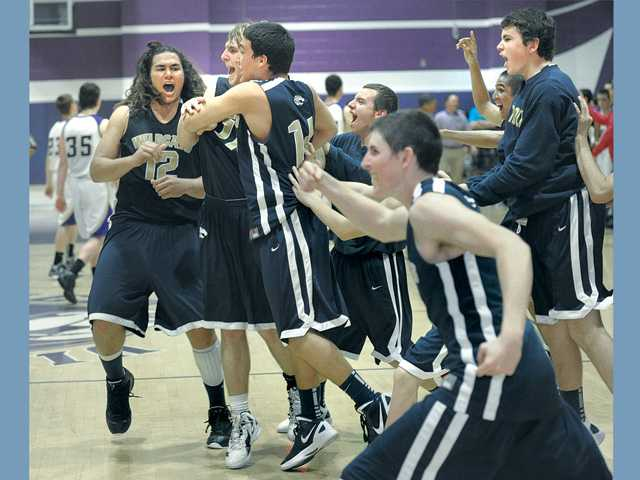 Members of the West Ranch boys basketball team run onto the court in celebration after clinching a share of the first Foothill League title in school history on Friday with an 86-79 win at Valencia.