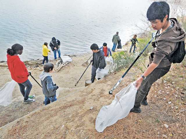 Cesar Lachica III, right, and a group from Arroyo Seco Junior High School in Valencia join more than 150 volunteers as they pick up trash along the shore of the Castaic Lake Lagoon as part of the Pride in the Lake Day presented by Friends of Castaic Lake on Saturday.