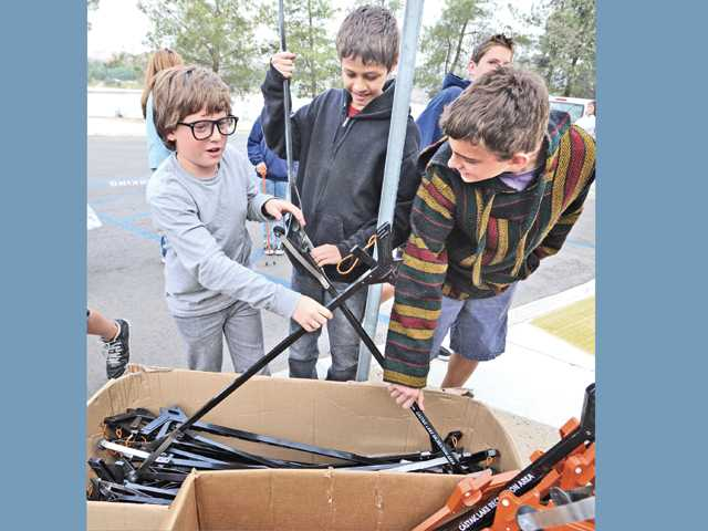 Thirteen-year-old Arroyo Seco Junior High School students, from left, Zakry Medvin, Victor Ramirez, and Josh DeLeon pick up their trash tongs.