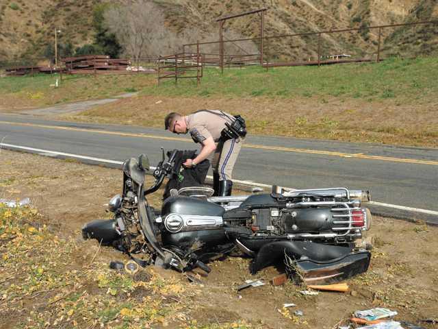 A CHP officer inspects the motorcycle.