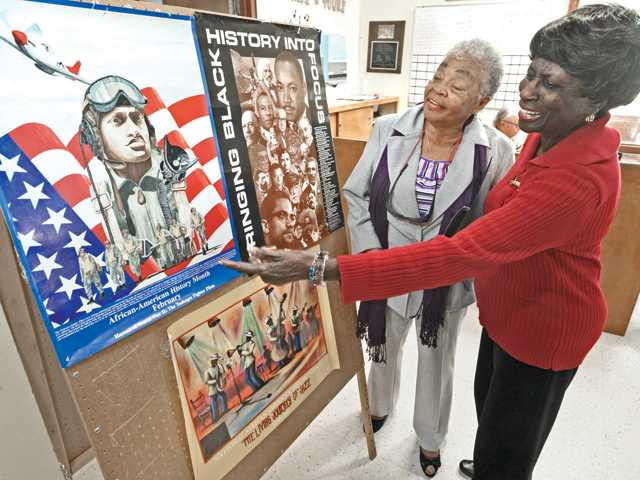 Billie Jean Curry, left, and Tommie Mae Ward examine posters on display for Black History Month at the entrance to the dining room of the Santa Clarita Valley Senior Center in Newhall on Wednesday.