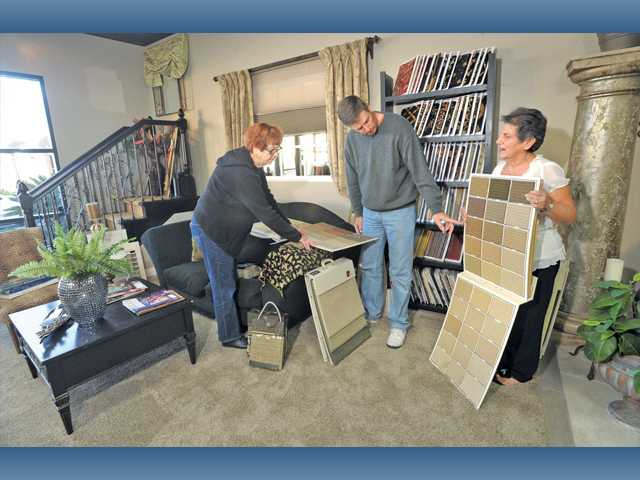 Sharon King, right, of Rudio Designz shows samples to Janet and Doug Garwood at the Valencia store Friday.