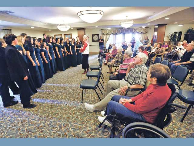 "Musical director Mary Purdy, center, leads the Canyon High School Madrigals as they sing ""My Romance"" for a group of seniors at Summerhill Villa Senior Living in Santa Clarita as part of Canyon High's Sweetheart Serenades program for Valentine's Day on Tuesday."