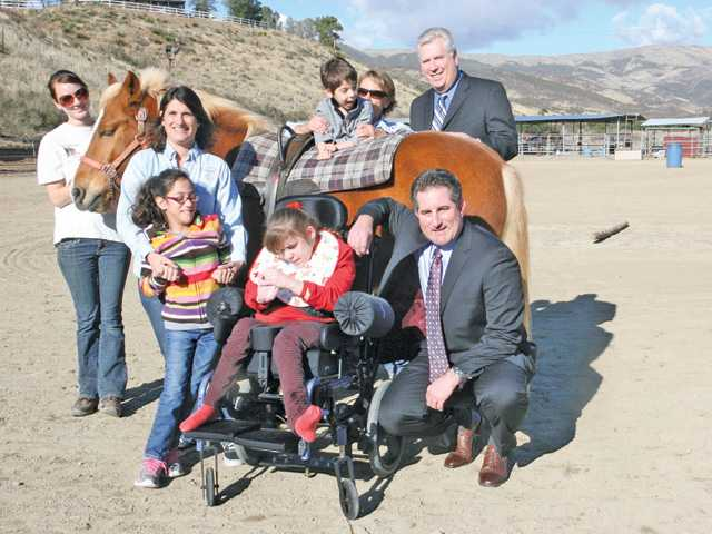 Bill Sloan, standing at right, and Greg Spencer, kneeling at right, of California United Bank with staff and children of Carousal Therapeutic Riding Ranch. The bank's recent $47,000 gift helped Carousel Ranch maintain its level of programs and services.