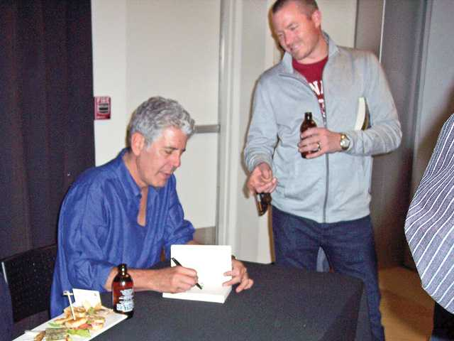 Anthony Bourdain signs a copy of his new book at event.