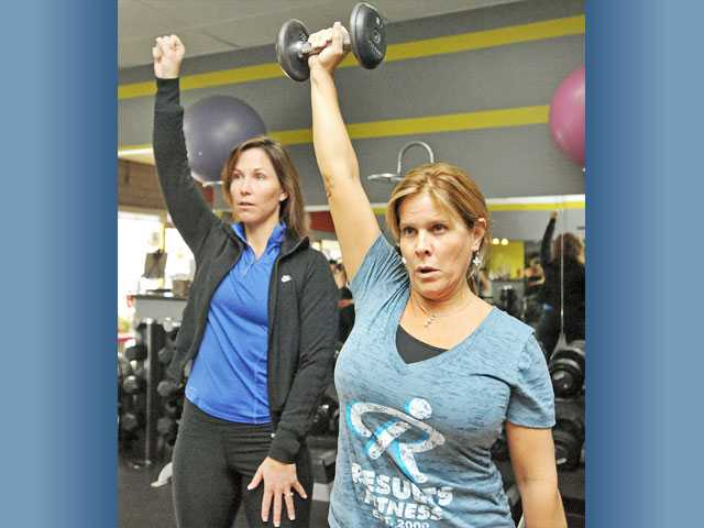 Rachel Cosgrove, left, guides Carolyn Fuess through a single arm overhead press exercise. Strength training is among the hottest fitness trends in 2012 for women.