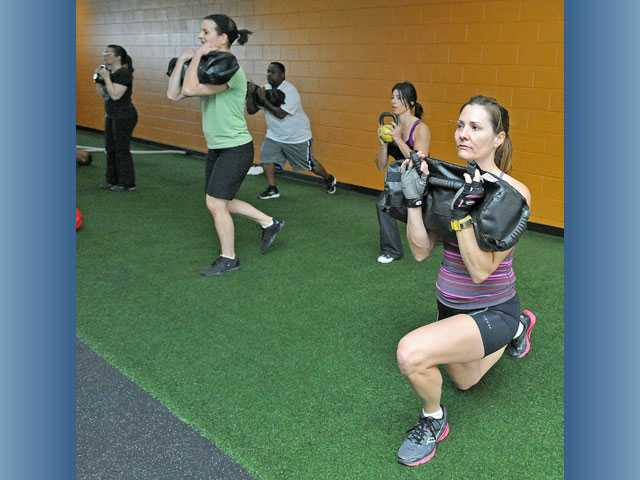 "Maria Palma, right, joins a group in working on sandbag reverse lunge. Reactive exercise and group personal training are among the newest and ""in"" types of fitness workouts."