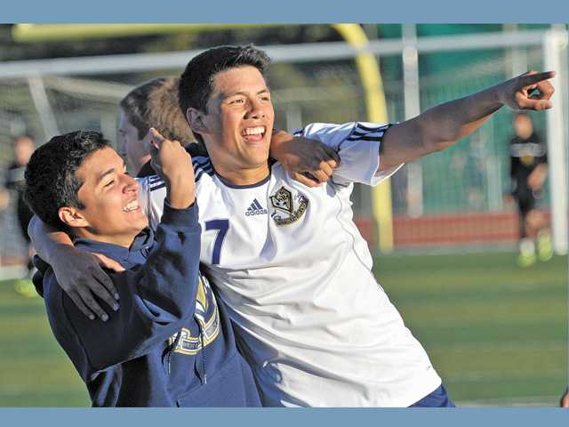 West Ranch High School's German Hernandez, left, hugs teammate Connor Ashlock, right, as he points to the fans in the stands after scoring the game-winning goal in the second extra period against Cabrillo High at West Ranch.