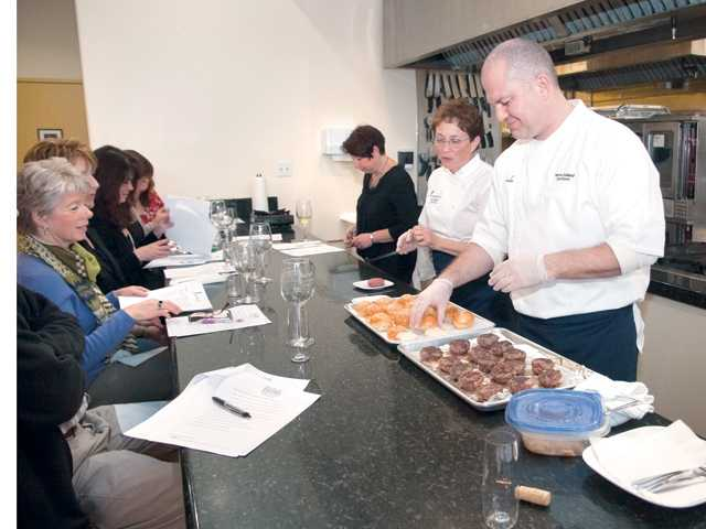 Kitchen Wizards owners and Le Cordon Bleu Chefs, Herve Guillard, right, and Judy Gilbert lead a class in the fine art of cuisine and wine pairing at their location in Valencia.