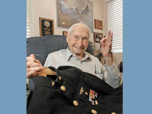 Johnson holds his U.S. Marine uniform from WWII.  He sits in front of a photo of a Dauntless dive bomber, the plane he flew in WWII.
