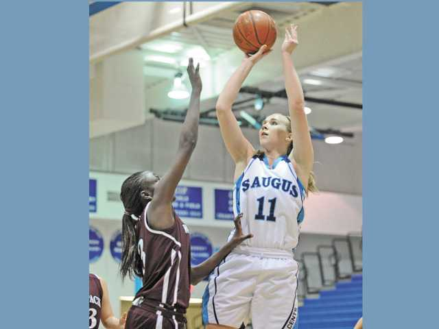 Saugus High's Megan Dawe (11) shoots against Claremont High defender Kegee Limbe at Saugus High on Saturday. Saugus won 57-29.