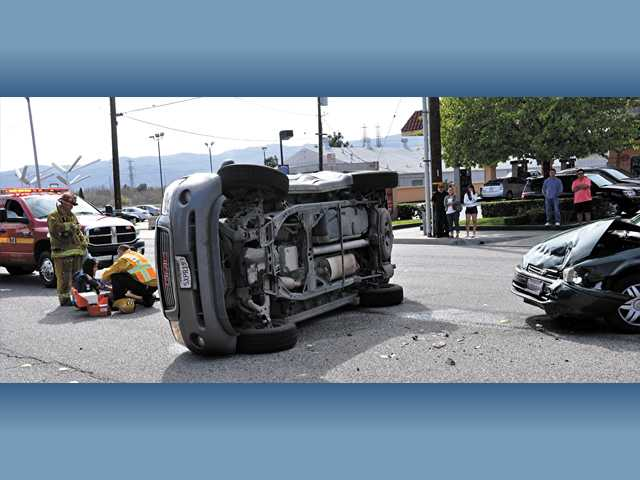 Los Angeles County firefighters evaluate occupants of vehicles involved in a collision in front of 26015 Bouquet Canyon Road on Sunday. A GMC SUV rolled over and three people sustained minor injuries.