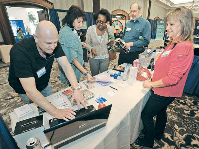 From left, Larry Barbro, Laura Kirchoff, Betty Wynn, Glenn Thornton and Bonnie Stauch discuss networking ideas at the HotSpot SCV booth.