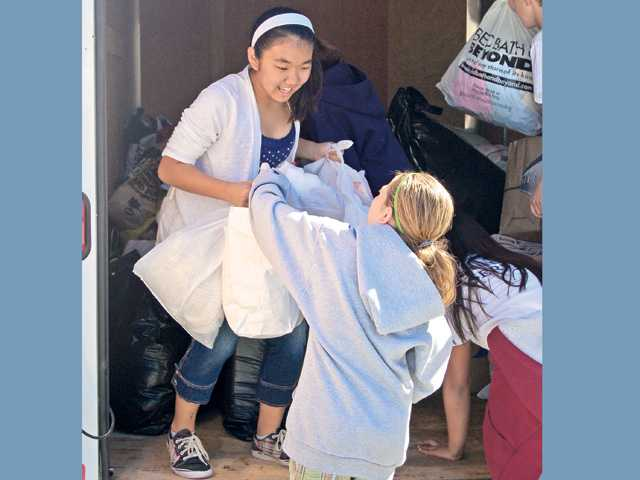 Sixth-grader Amanda Yamamoto helps load up the AngelDogs Foundation trailer with help from her fellow Student Service program members.