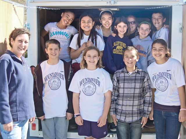 Lisa Tipton, director of AngelDogs Foundation, a nonprofit mobile spay/neuter clinic and deaf-dog rescue network in Newhall, with members of the Mountainview Elementary Student Service program. The group donated more than 200 blankets, towels, toys, collars and leashes as part of Project Puppy Love, which was loaded in the AngelDogs Foundation trailer on Feb. 10.
