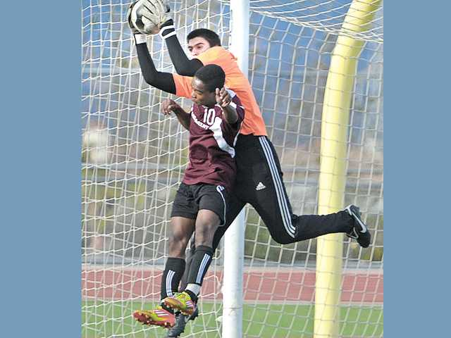 Paramount High School's Tyrone Pitter (10) collides with West Ranch goalkeeper Alex Manzo as he grabs a shot on goal at West Ranch High on Tuesday.