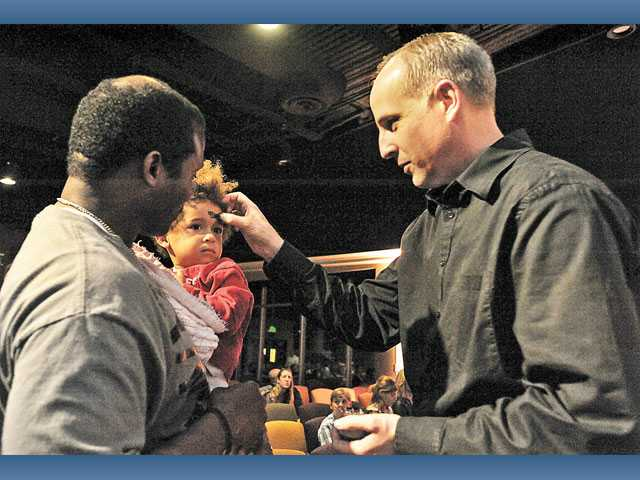 "Pastor Russ Klehn, right, places a cross of ash on the forehead of Haeven Cayette, 2, as Rodginald Cayette, of Valencia, holds her during an Ash Wednesday service at NorthPark Community Church in Valencia on Wednesday. About 300 people gathered at the church to mark the beginning of the Lenten season, the weeks leading up to Easter. ""It's a traditional service throughout the church. We don't do a lot of traditional things, but this is something that we feel is important to start off this season,"" Klehn said. ""It's a night of preparation, preparing our hearts for what's going to come over the next six weeks or so."""