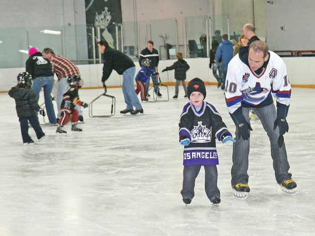 Lloyd Eisler, right, coaches his son Magnus, 5, as the two skate across the ice at the Los Angeles Kings Valley Ice Center in Panorama City. Guests to Magnus' birthday party joined the duo on the ice as part of the party package.