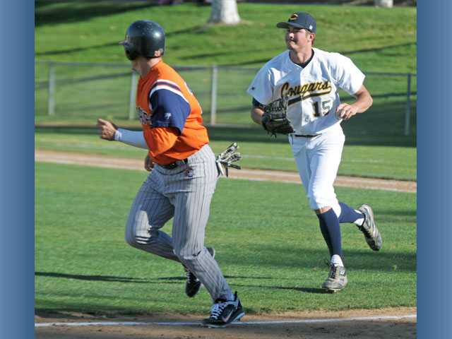 College of the Canyons pitcher Justin Phelps, right, pursues Orange Coast outfielder Bijan Rademacher on a pick-off play during Thursday's game at COC.
