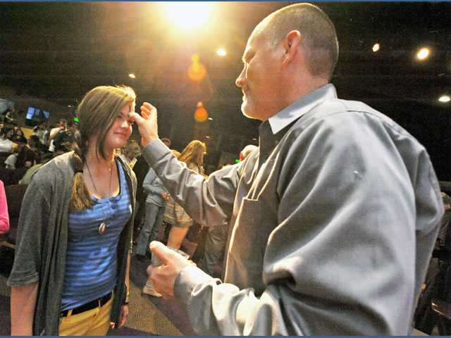 Bethany Steele, 12, of Castaic, left, receives a cross of ash on her forehead from Pastor Matt Stemme, right.