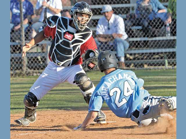 Hart High catcher Baggio Saldivar, left, makes the tag at home plate on Quartz Hill baserunner Brandon Murachanian on Friday at Hart High School.