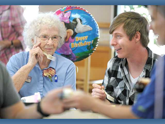 Maxine Coleman, left, shares a moment with her grandson Eron Coleman, 29, of Fort Worth, Texas, as they enjoy cake for her 90th birthday at Wendy's in Saugus on Friday.