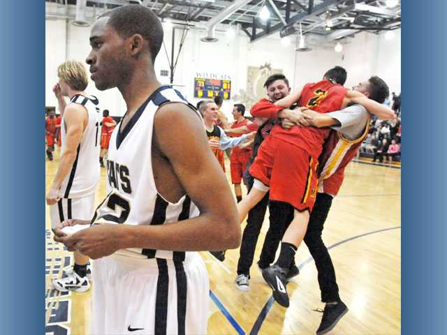 West Ranch point guard Bo Vaughn walks away from the court as members of Mission Viejo celebrate following their 81-77 win over the Wildcats in overtime of a CIF-Southern Section Division IA quarterfinal game on Friday at West Ranch High School.