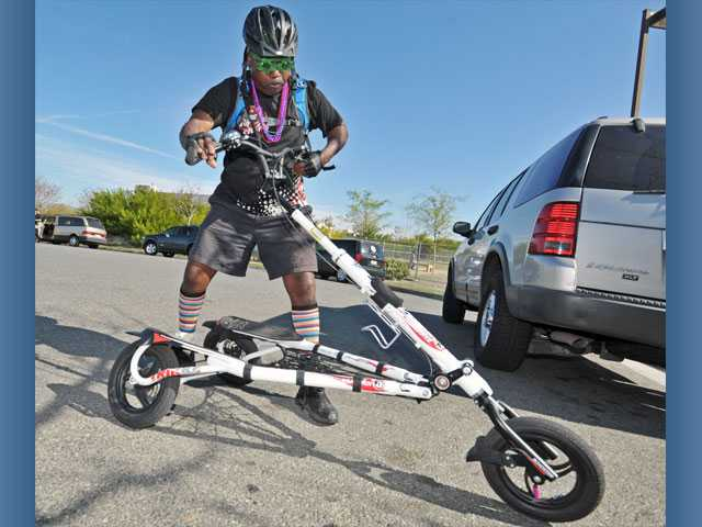 Bill Green, of Temple City, folds his Trikke vehicle after meeting with fellow enthusiasts at the Santa Clarita Sports Complex on Saturday. The Trikkers chose from a 18.6-mile ride, a 10.5-mile ride and 6.6-mile ride.