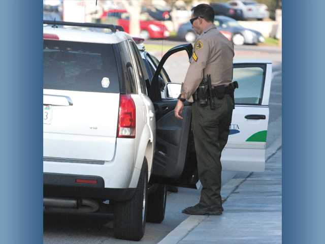 A Santa Clarita Valley Sheriff's Station deputy searches the vehicle of two burglary suspects on Creekside Road in Valencia on Sunday. Security at a nearby Target department store recognized the suspects in the store from a prior day's burglary and called deputies, who arrested the suspects.