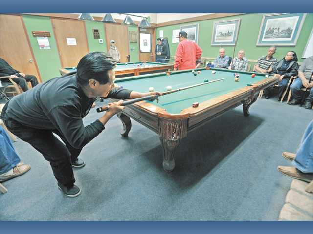 June Micu, left, lines up a shot during the billiards tournament held at the SCV Senior Center on Thursday.
