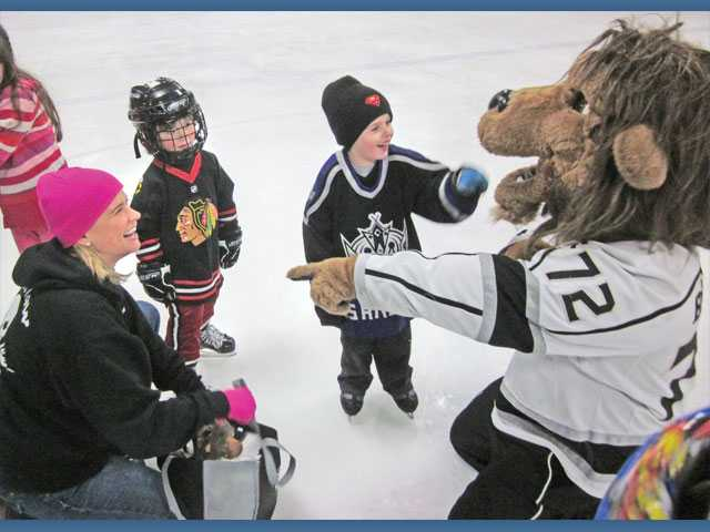 From left, Kristy Swanson, Liam Zeller, 5, Magnus Eisler, 5, and Bailey the Lion, the mascot of the Los Angeles Kings professional hockey team, at the L.A. Kings Valley Ice Center.