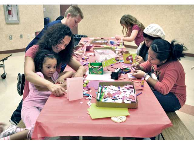 West Creek Academy students and parents work on hand-made Valentine's Day greetings for Help The Children. The PTA and students organized a food drive and made goody bags on Feb. 10 to help the local nonprofit organization's effort to aid families in need.
