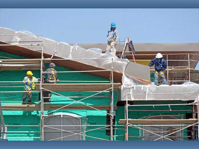 Construction crews continue work on the Old Town Newhall Library on Tuesday.