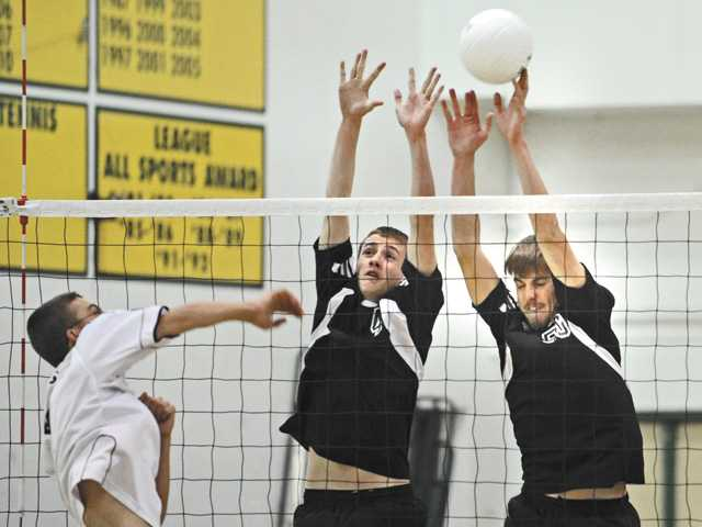 Cowboys teammates Andy Kern, center, and Austin Van Nattan, right, deflect a kill attempt by Quartz Hill's Matt Greene on Tuesday at Canyon High School.