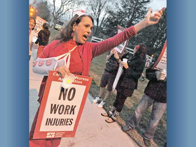 """Registered nurse Clare Montagna chants as she and fellow nurses protest Henry Mayo Newhall Memorial Hospital's """"team nursing"""" staffing program, outside the Valencia hospital on Wednesday."""