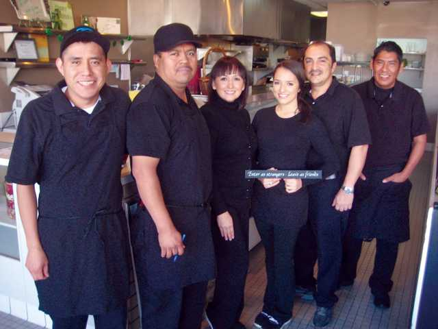 "Most of the Cathy's family, left to right, Ulises Gonzalez, Maxx Ventura, Lupita Traba, Valerie Traba, Val Traba and Tony Cruz. Valerie Traba holds the restaurant's motto, ""Enter as strangers. Leave as friends."""