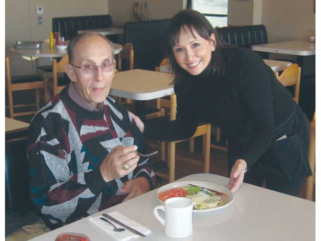Lupita Traba serves Edwin Dobkowski his Green Chili Omelete. Dobkowski is a longtime customer.